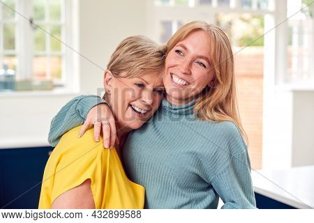 Senior Woman Greeting And Hugging Grown Up Adult Daughter At Home