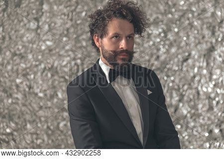 attractive young groom in black tuxedo looking up and side while sitting against tinfoil background in studio