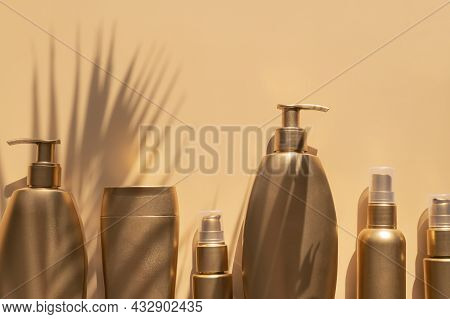 Golden Clean Bottles Of Cosmetics, Sun Shade From Palm Leaf On Beige Background. Cosmetic Mock Up Bo