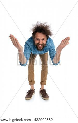 casual handsome man leaning forward with open arms against white background