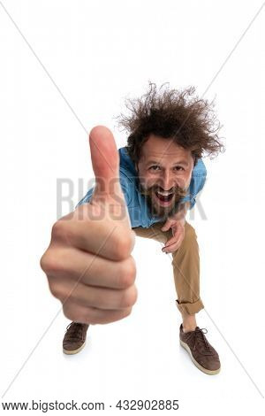 attractive casual man leaning forward and giving a thumbs up against white background