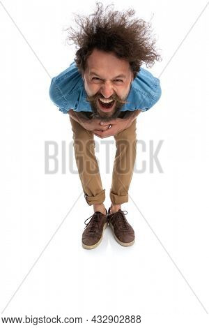 young casual man leaning forward and laughing at the camera on white background