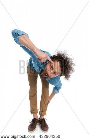 attractive casual man leaning forward and pointing at his head on white background