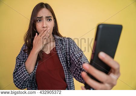 Close Up Of A Woman With Long Hair Using A Mobile Phone Shocked When She Sees A Mobile Phone Screen
