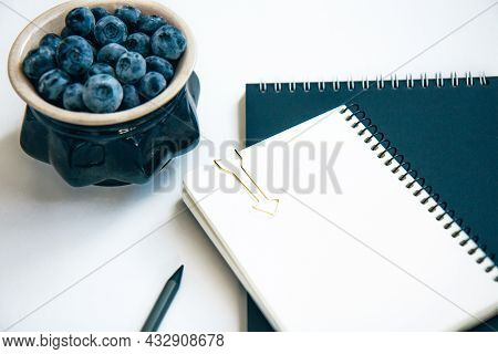 Black And White Notepads And Blueberries In A Ceramic Bowl Isolated On White Background