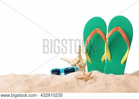 Green Flip Flops, Starfishes And Sunglasses On Sand Against White Background