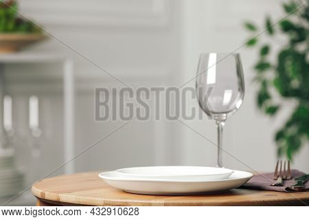 White Plates And Wineglass Served For Dinner On Wooden Table