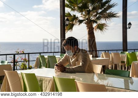 Lockdown, Quarantine Regulations And Closure Of Restaurants In Cyprus. Sad Masked Man Sits In Empty