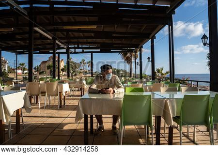 Lonely Sad Masked Man Sits And Uses Smartphone Himself In Empty Restaurant In Cyprus At Agios Georgi