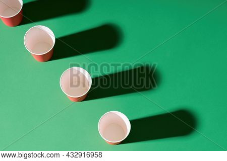 Top View Of Red Paper Cup In Row On Green Background With Shadows