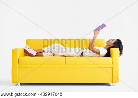 Pretty Asian Woman Reading Book Lying At Cozy Yellow Couch