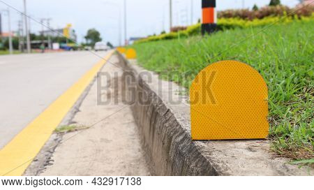 Reflective Stickers On The Side Of The Road. A Yellow Metal Plate Mounted On The Side Of The Road Ac