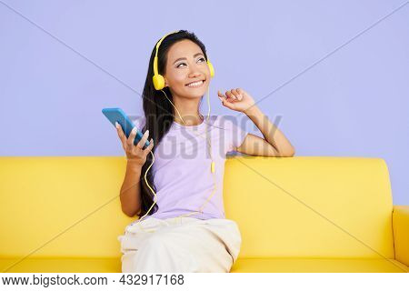 Pretty Young Woman Listening To Music With Cell Phone And Relaxing While Sitting On Sofa