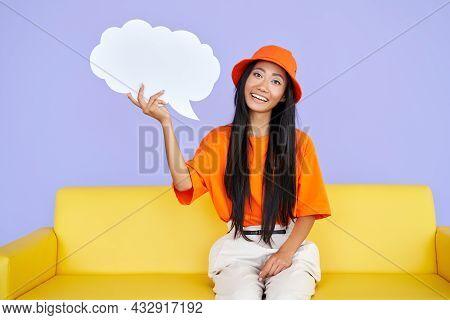 Beautiful Hipster Girl Holding Empty Speech Bubble Sitting On Sofa