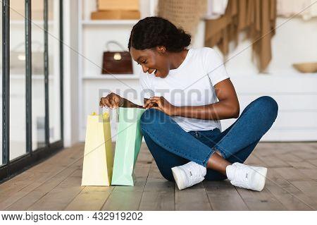Cheerful Black Shopaholic Lady Opening Shopper Bag In Wardrobe Room