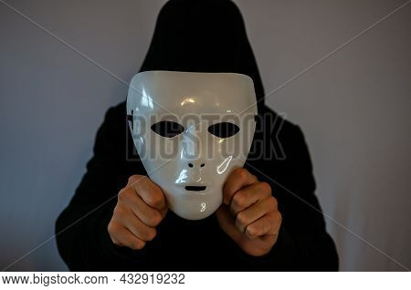 Man With Black Hood Holding An Anonymous White Mask On Dark Background
