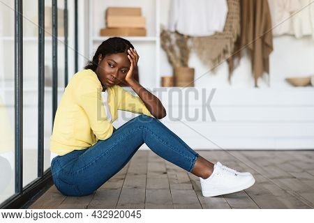 Unhappy African American Lady Sitting Near Closet At Home