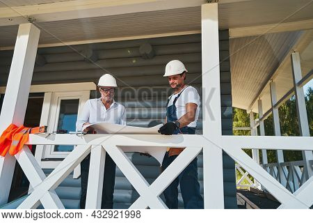 Pair Of Construction Engineers Reading Drawings On Porch