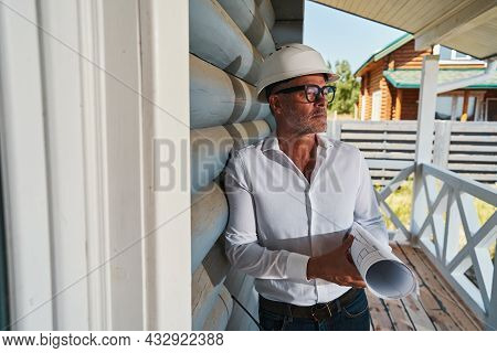Intelligent Engineer With Drawings Staring Outside From Porch