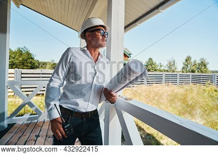 Housebuilder With Drawings In Arms Leaning On Porch Railings