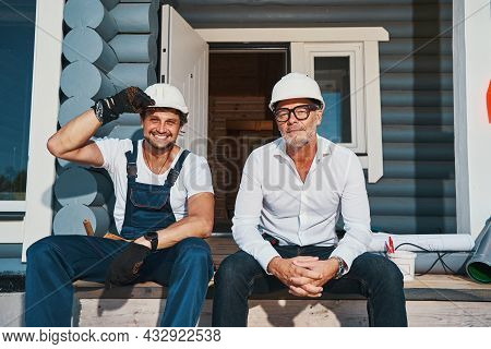 Builder Adjusting Har Hat While Sitting On Porch With Engineer