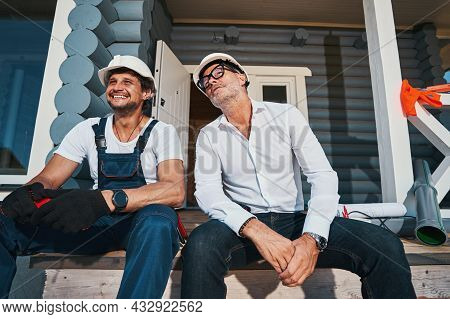 Two Men Watching Something From Stairs Of House Porch