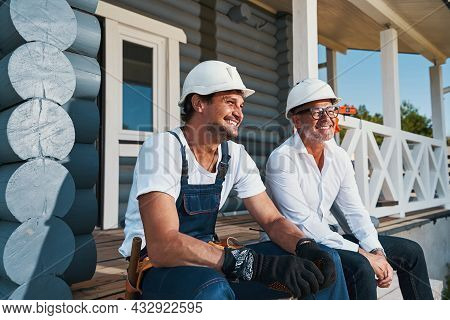 Happy Builders Are Relaxing On Porch Stairs