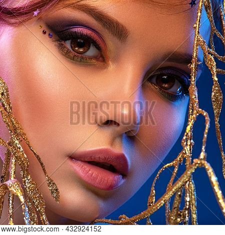 Stylish fashion model with a golden decoration around her face. Beauty style. Art portrait of a beautiful woman with bright makeup. Closeup model face with vivid eye make-up.