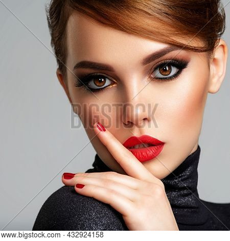 Beautiful brunette girl with red lips and short, slick hair. Pretty young sensual woman with red nails. Closeup portrait of a model with bright makeup on a face. Attractive female posing at studio.