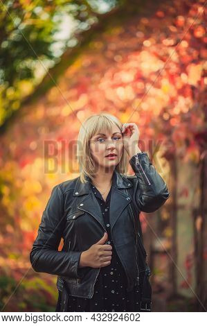 Young Woman With Bob Haircut And Fringe In A Black Leather Jacket Is Standing In An Abandoned Greenh