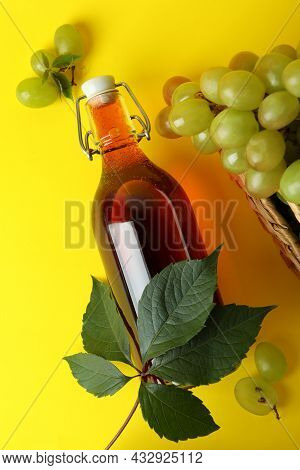 Bottle Of Vinegar And Basket With Grape On Yellow Background