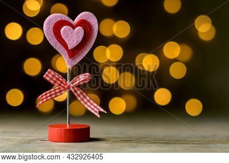 Valentine's Day Concept. A Pink Red Heart-shaped Note Holder On A Rustic Wooden Table In Front Of A