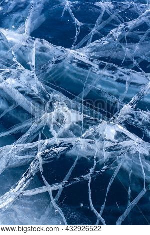 Natural Thick Clear Ice With Deep Cracks. Blue Transparent Ice With White Cracks. Vertical.