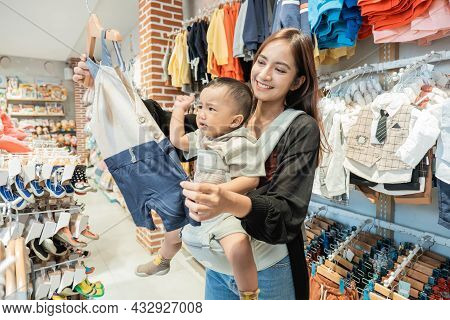 Indonesian Mother Shopping Clothes For Her Son In The Baby Boutique Store