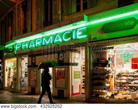 Nice, France - Nov 22, 2019: Single Man With Umbrella In Front Of Pharmacy Drug Store With Neon Gree