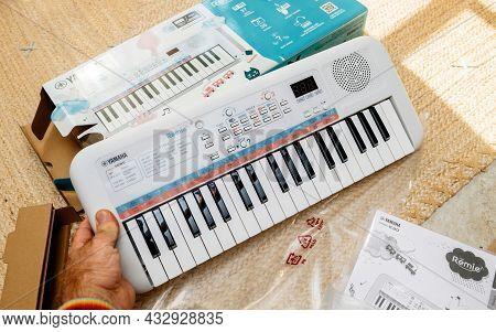 Paris, France - Sep 8, 2021: Pov Male Hand Unboxing New Yamaha Remie Digital Keyboard Pss-e30 For Ki