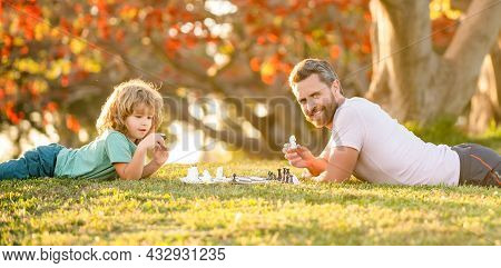 Tutorship. Dad And Kid Play Logic Game. Father And Son Playing Chess Relaxing On Grass.