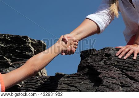 Woman Getting Help On Hike Overcoming Obstacle. Hikers Climbing On Rock, Mother Giving Hand And Help