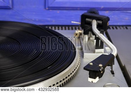 Close Up Of Vintage Turntable Vinyl Record Player By Blue Wall.
