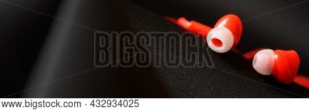 Red Earbuds On A Dark Textile Surface. The Concept Of Earbuds In A Pocket Or Bag. Web Banner. Close-
