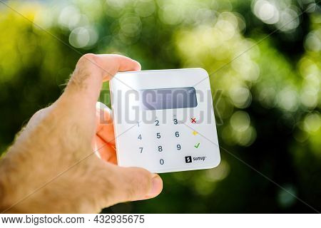 Paris, France - Sep 8, 2021: Male Hand Holding New Sumup Emv Card Reader Which Can Read Magnetic Str