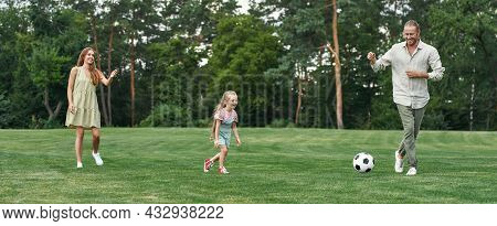 Lovely Young Family Playing Football On The Grass Field In The Park On A Summer Day. Childhood, Spor