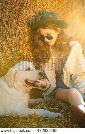 Romantic hippie girl sits by a haystack in a field with her beloved dog. Light from the setting sun. The spirit of adventure and freedom.