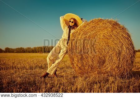 Autumn and summer fashion. Full length portrait of a beautiful fashion model girl posing in boho style clothes in a field next to a haystack.