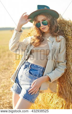 Modern hippie and bohemian style. Portrait of a romantic girl standing by a haystack in a field in the rays of the setting sun. Summer and autumn fashion.