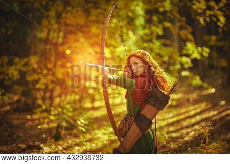 Beautiful red-haired archer girl from the middle ages stands in the autumn forest and shoots a bow. Celtic culture. Fantasy world.