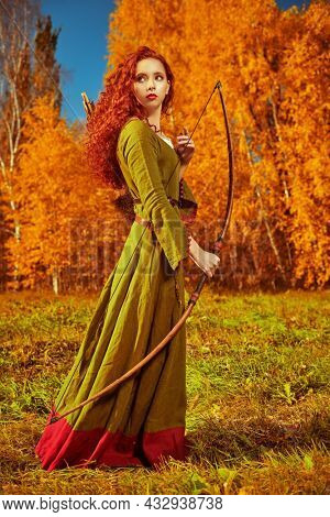Fantasy world. Full length portrait of a beautiful red-haired girl archer of the Middle Ages standing by a golden autumn forest. Celtic culture. Autumn nature.