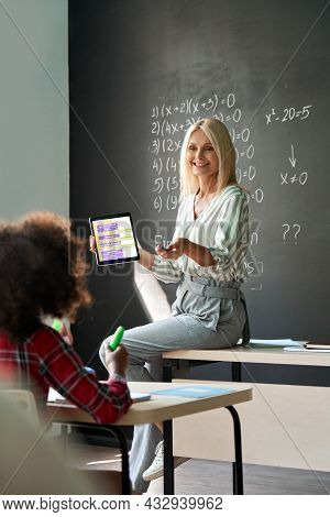 Smiling Female Teacher Demonstrating New Maths Task Holding Using Tablet Device To Elementary Divers