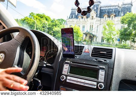 In Car Dashboard View With Smartphone Showing Waze Maps To Show The Way Thru The City. Driver Using