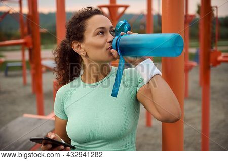 Beautiful Sporty Latin American Woman With Athletic Physique Holding A Smartphone In One Hand And Dr